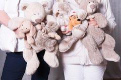 Οι θηλυκοί αρωγοί προσφέρουν τα παιχνίδια στα παιδιά προσφύγων Στοκ εικόνα με δικαίωμα ελεύθερης χρήσης