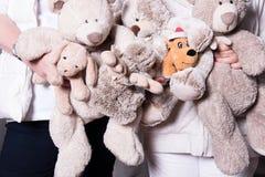 Οι θηλυκοί αρωγοί προσφέρουν τα παιχνίδια στα παιδιά προσφύγων Στοκ φωτογραφία με δικαίωμα ελεύθερης χρήσης
