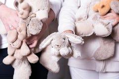 Οι θηλυκοί αρωγοί προσφέρουν τα παιχνίδια στα παιδιά προσφύγων Στοκ Εικόνες