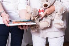 Οι θηλυκοί αρωγοί προσφέρουν τα παιχνίδια στα παιδιά προσφύγων Στοκ Φωτογραφίες