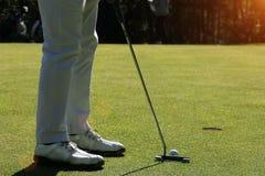 Οι θολωμένοι παίκτες γκολφ βάζουν το γκολφ στο γήπεδο του γκολφ βραδιού στο Τ στοκ εικόνα