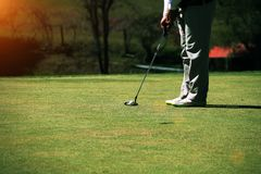 Οι θολωμένοι παίκτες γκολφ βάζουν το γκολφ στο γήπεδο του γκολφ βραδιού στο Τ στοκ φωτογραφίες