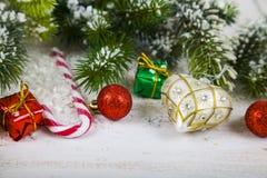 Οι διακοσμήσεις, τα δώρα και το έλατο Χριστουγέννων διακλαδίζονται στο χιόνι σε ένα W Στοκ Εικόνα