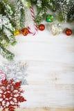 Οι διακοσμήσεις, τα δώρα και το έλατο Χριστουγέννων διακλαδίζονται στο χιόνι σε ένα W Στοκ Φωτογραφία