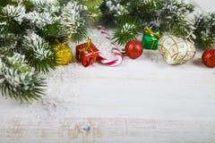 Οι διακοσμήσεις, τα δώρα και το έλατο Χριστουγέννων διακλαδίζονται στο χιόνι σε ένα W Στοκ Φωτογραφίες