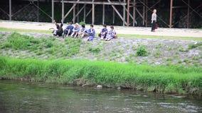 Οι ιαπωνέζοι κάθονται και μιλούν στην όχθη ποταμού του ποταμού Kamo στο Κιότο, Ιαπωνία απόθεμα βίντεο