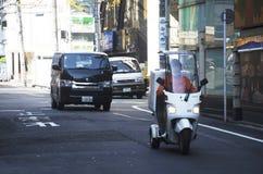 Οι ιαπωνέζοι που οδηγούν το αυτοκίνητο και που οδηγούν τη μοτοσικλέτα στο δρόμο μέσα Στοκ φωτογραφία με δικαίωμα ελεύθερης χρήσης