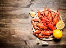 Οι λιχουδιές τροφίμων Βρασμένοι αστακοί με τις φέτες του λεμονιού στοκ εικόνα