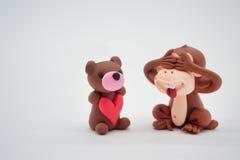 Οι ιδιαίτερες προσοχές κουκλών πιθήκων και αντέχουν την κούκλα κρατώντας την κόκκινη καρδιά Στοκ Φωτογραφία