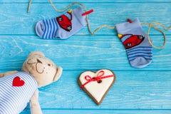 Οι κάλτσες μωρών στη γραμμή ενδυμάτων, καρδιά μελοψωμάτων και αντέχουν Στοκ Εικόνες