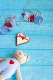 Οι κάλτσες μωρών στη γραμμή ενδυμάτων, καρδιά μελοψωμάτων και αντέχουν Στοκ Φωτογραφία