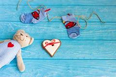 Οι κάλτσες μωρών στη γραμμή ενδυμάτων, καρδιά μελοψωμάτων και αντέχουν Στοκ Εικόνα