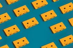 Οι κίτρινες αναδρομικές ακουστικές ταινίες κασετών στο μπλε υπόβαθρο, επίπεδο βάζουν Δημιουργική έννοια της αναδρομικής τεχνολογί Στοκ Εικόνες