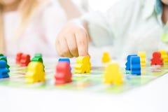 οι κίτρινοι άνθρωποι λογαριάζουν υπό εξέταση του παιδιού τα κόκκινα, μπλε, πράσινα ξύλινα τσιπ στα παιδιά παίζουν - έννοια επιτρα στοκ εικόνα