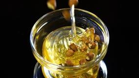 Οι καθαρές μέλισσες μελιού χύνουν σε ένα κύπελλο και προσθέτουν έπειτα το καθαρισμένο φουντούκι, φουντούκια φιλμ μικρού μήκους