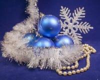 Οι καθορισμένες μπλε όμορφες σφαίρες έτους ` s γυαλιού νέες, λαμπρό tinsel, και ένα μαργαριτάρι διακοσμούν με χάντρες σε ένα μπλε Στοκ φωτογραφίες με δικαίωμα ελεύθερης χρήσης