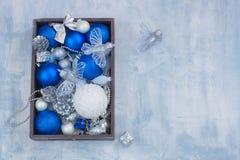 Οι καθορισμένοι ασημένιοι άσπροι και μπλε κώνοι παιχνιδιών σφαιρών διακοσμήσεων καρτών Χριστουγέννων παρουσιάζουν στο ξύλινο κιβώ Στοκ Φωτογραφία