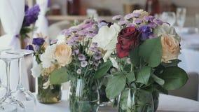Οι καλές ανθοδέσμες με τα ζωντανά λουλούδια είναι στον πίνακα στο εστιατόριο φιλμ μικρού μήκους