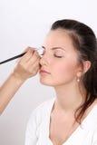 Οι καλλιτέχνες σύνθεσης εφαρμόζουν makeup το μοντέλο στοκ εικόνα
