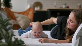 Οι καλύτερες στιγμές από τη ζωή, μια αγαπώντας ευτυχής νέα μητέρα αγκαλιάζει έναν νοσηλευτικό γιο, σε ένα λευκό σαν το χιόνι κάλυ απόθεμα βίντεο