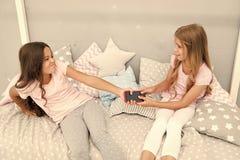 Οι καλύτεροι φίλοι ή οι αδελφές παιδιών κοριτσιών φορούν το pajamacan όχι ενιαίο smartphone μεριδίου Τα παιδιά στην πυτζάμα παλεύ στοκ φωτογραφίες