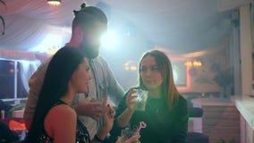 Οι καλύτεροι φίλοι που απολαμβάνουν το κόμμα στη λέσχη και πίνουν τα κοκτέιλ στα φω'τα υποβάθρου απόθεμα βίντεο