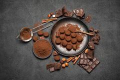 Οι καραμέλες τρουφών σοκολάτας, τα κομμάτια σοκολάτας και το κακάο κονιοποιούν στο σκοτεινό συγκεκριμένο υπόβαθρο στοκ εικόνα με δικαίωμα ελεύθερης χρήσης