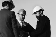 Οι κατασκευαστές κρατούν το φάκελλο συνδετήρων Έννοια οικοδόμησης και εφαρμοσμένης μηχανικής στοκ εικόνες