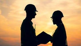 Οι κατασκευαστές που μιλούν σε ένα υπόβαθρο ηλιοβασιλέματος, κλείνουν επάνω απόθεμα βίντεο