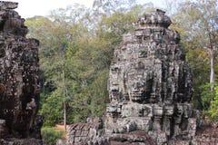 Οι καταστροφές ενός παλαιού ναού με τα κεφάλια και τα πρόσωπα πετρών σε Cambodi Στοκ Εικόνα