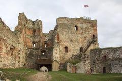Οι καταστροφές της διαταγής Castle Livonia χτίστηκαν στο μέσο του 15ου αιώνα Μπαούσκα Λετονία το φθινόπωρο Λετονική σημαία Στοκ Φωτογραφία