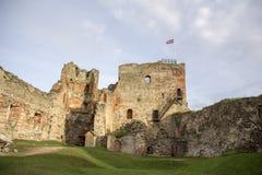 Οι καταστροφές της διαταγής Castle Livonia χτίστηκαν στο μέσο του 15ου αιώνα Μπαούσκα Λετονία το φθινόπωρο Λετονική σημαία Στοκ εικόνα με δικαίωμα ελεύθερης χρήσης