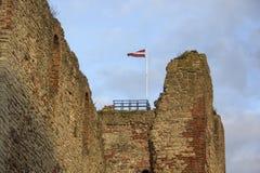 Οι καταστροφές της διαταγής Castle Livonia χτίστηκαν στο μέσο του 15ου αιώνα Μπαούσκα Λετονία το φθινόπωρο Λετονική σημαία Στοκ Εικόνες