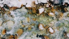 Οι κατώτατες πέτρες πλένονται από το ρέοντας νερό από το ρυάκι φιλμ μικρού μήκους