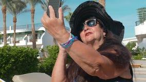 Οι καυκάσιοι ανώτεροι θηλυκοί ηλικιωμένοι σε ένα μαύρο καπέλο κάνουν ένα selfie σε ένα smartphone και κάνουν ηλιοθεραπεία στον ήλ φιλμ μικρού μήκους
