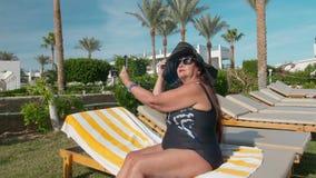 Οι καυκάσιοι ανώτεροι θηλυκοί ηλικιωμένοι σε ένα μαύρο καπέλο κάνουν ένα selfie σε ένα smartphone και κάνουν ηλιοθεραπεία στον ήλ απόθεμα βίντεο