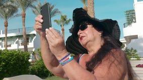 Οι καυκάσιοι ανώτεροι θηλυκοί ηλικιωμένοι στο μαύρο καπέλο θέτουν για ένα selfie σε ένα smartphone και κάνουν ηλιοθεραπεία στον ή φιλμ μικρού μήκους
