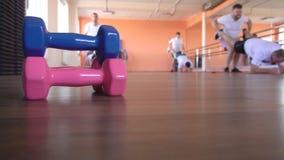 Οι καυκάσιοι αρσενικοί φίλοι παίζουν τον αθλητισμό σε ένα σύγχρονο κέντρο ικανότητας με τη βοήθεια ενός όμορφου εκπαιδευτή κοριτσ απόθεμα βίντεο