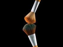 Οι καλλυντικές βούρτσες makeup στη μαύρη σκιά σκονών παφλασμών έκρηξης λάμψης υποβάθρου κοκκινίζουν Στοκ Εικόνα