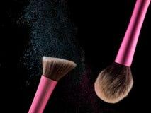 Οι καλλυντικές βούρτσες makeup στη μαύρη σκιά σκονών παφλασμών έκρηξης λάμψης υποβάθρου κοκκινίζουν Στοκ Φωτογραφίες