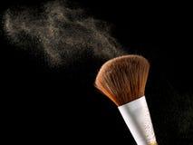 Οι καλλυντικές βούρτσες makeup στη μαύρη σκιά σκονών παφλασμών έκρηξης λάμψης υποβάθρου κοκκινίζουν Στοκ Εικόνες