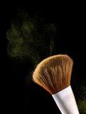 Οι καλλυντικές βούρτσες makeup στη μαύρη σκιά σκονών παφλασμών έκρηξης λάμψης υποβάθρου κοκκινίζουν Στοκ Φωτογραφία