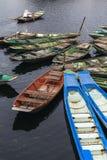 Οι κενές βάρκες κωπηλασίας σταματούν πέρα από τον ποταμό με ένα άτομο που φορά το άσπρο πουκάμισο και την κωνική βάρκα κωπηλασίας Στοκ εικόνα με δικαίωμα ελεύθερης χρήσης