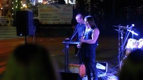 Οι κιθάρες παιχνιδιών ορχηστρών ροκ οδών, τύμπανα και τραγουδούν τα τραγούδια τη νύχτα απόθεμα βίντεο