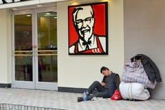 Οι κινεζικοί άστεγοι κάθονται επάνω έξω από το εστιατόριο γρήγορου φαγητού της KFC στοκ εικόνες