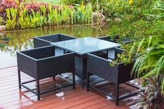 Οι κλασικοί καρέκλες και ο πίνακας ινδικού καλάμου στο ξύλινο μπαλκόνι εκτός από τη μικρή όμορφη λίμνη σε πράσινες εγκαταστάσεις  στοκ φωτογραφίες με δικαίωμα ελεύθερης χρήσης