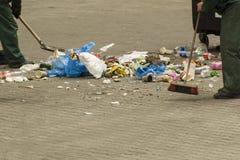 Οι κοινοτικοί εργαζόμενοι υπηρεσιών καθαρίζουν την οδό από τα απορρίματα στοκ εικόνα