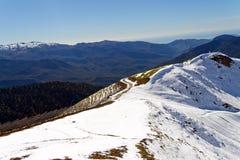 Οι κορυφές των βουνών που καλύπτονται με το χιόνι Οι κλίσεις είναι thic στοκ φωτογραφία με δικαίωμα ελεύθερης χρήσης