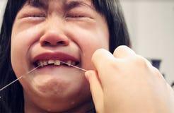 Οι κραυγές παιδιών ως ενήλικος προσπαθούν να εξαγάγουν ένα Lose δόντι μωρών με Στοκ εικόνα με δικαίωμα ελεύθερης χρήσης