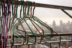 Οι κρεμάστρες υφασμάτων στη γραμμή υφασμάτων στο μπαλκόνι του κατοικημένου κτηρίου σε μια βροχερή ημέρα με το μουτζουρωμένο υπόβα Στοκ φωτογραφία με δικαίωμα ελεύθερης χρήσης